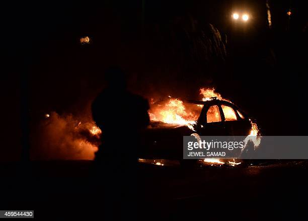 A police car burns after being set on fire during clashes between police and protesters over decision in the shooting death 18yearold Michael Brown...