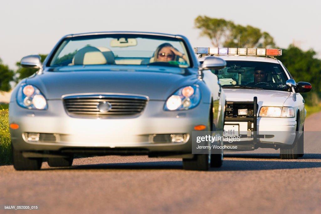 Police car chasing a convertible car