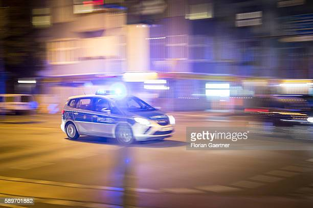 A police car drives over a crossroad with emergency lights at night on August 09 2016 in Berlin Germany