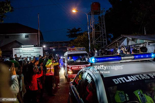 A police car escorts an ambulance carrying a coffin containing the body of one of the eight drug traffickers leaves Wijaya Pura port after the...