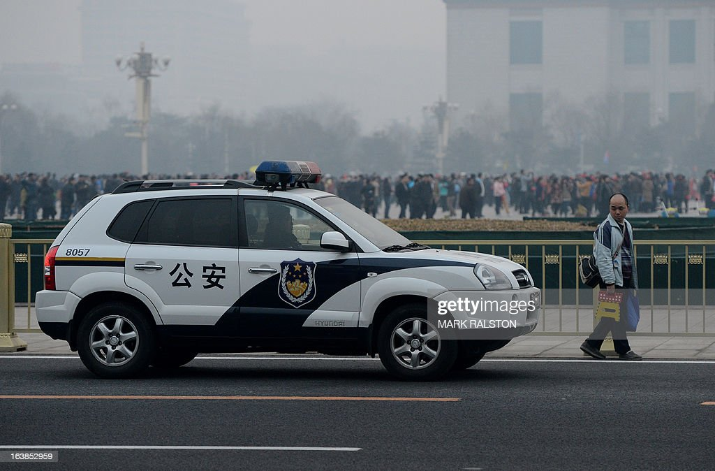 A police car follows a man trying to gain entry to Tiananmen Square before the closing session of the National People's Congress (NPC) at the Great Hall of the People in Beijing on March 17, 2013. New Chinese Premier Li Keqiang steps into the media spotlight for a rare press conference, as the annual meeting of the country's rubber-stamp parliament closes. AFP PHOTO/Mark RALSTON