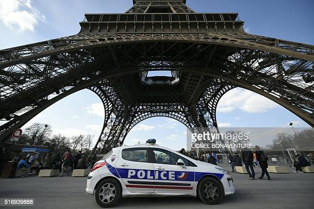 A police car is parked near the Eiffel tower on March 22 2016 in Paris / AFP / LIONEL BONAVENTURE