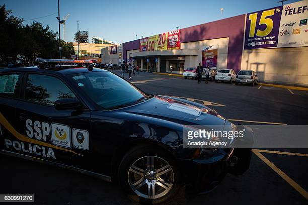 A police car is seen guarding outside a store during the protests related with the increase of the prices of the gasoline in Mexico on Mexico City...