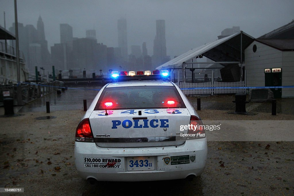 A police car looks out over Manhattan from near the Brooklyn Bridge as Hurricane Sandy begins to affect the area on October 29, 2012 in the in Brooklyn of New York City. The storm, which threatens 50 million people in the eastern third of the U.S., is expected to bring days of rain, high winds and possibly heavy snow. New York Governor Andrew Cuomo announced the closure of all New York City bus, subway and commuter rail service as of Sunday evening.