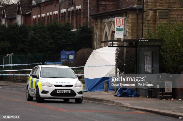 A police car parked close to a forensic tent in in Old Trafford Greater Manchester where an 18 year old was stabbed to death yesterday