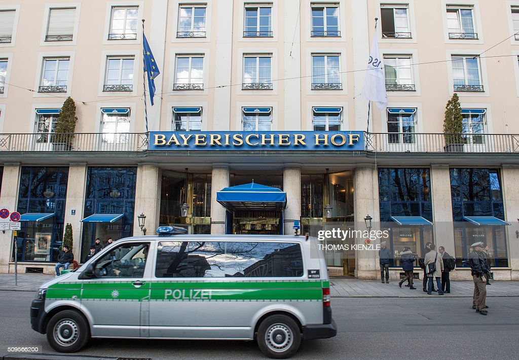A police car passes by the Bayerischer Hof hotel, the location for the 52nd Munich Security Conference (MSC), in Munich, southern Germany, on February 11, 2016. The Munich Security Conference takes place here from February 12 und until February 14, 2016. / AFP / THOMAS KIENZLE