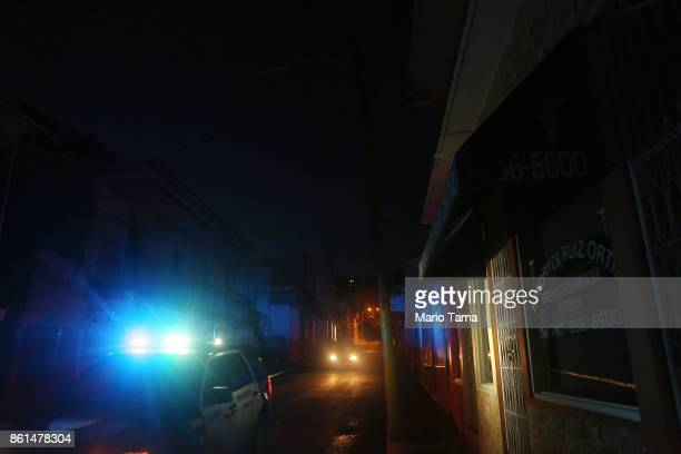 A police car patrols in an area with a sporadic electricity supply as a nightly curfew remains in effect on October 14 2017 in Yauco Puerto Rico...