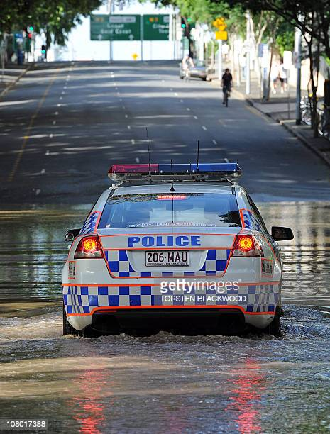 A police car patrols the neardeserted city centre as flood waters inundate Brisbane on January 13 2011 Australia's thirdlargest city awoke to a 'war...