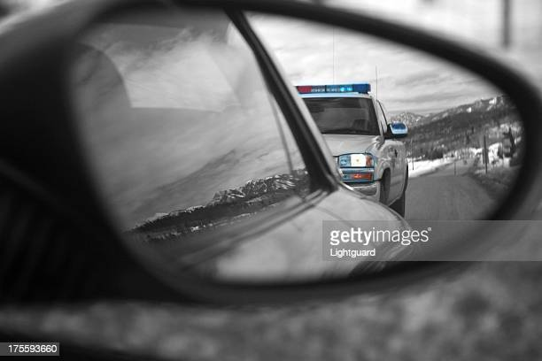 Police car reflected in side mirror of speeding car