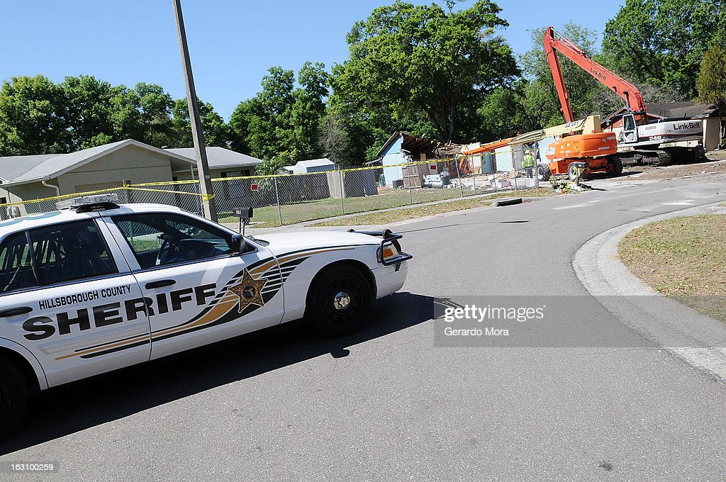A police car sits in front of the home where a sinkhole swallowed Jeffrey Bush on March 4, 2013 in Seffner, Florida. Jeff Bush, presumed dead after a sinkhole, estimated at 60 feet deep, opened under his bedroom while he was sleeping in the home. Demolition crews are working to raze the house, recover possessions, and stabilize the now-shaky ground.