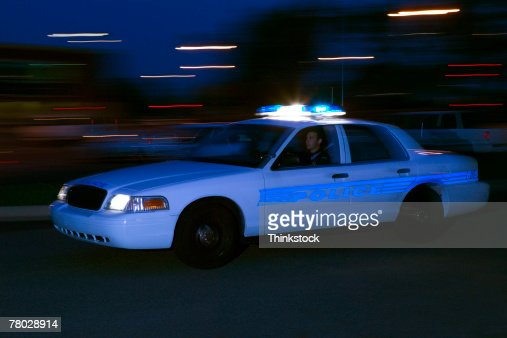 A police car speeds past the viewer, motion blurred