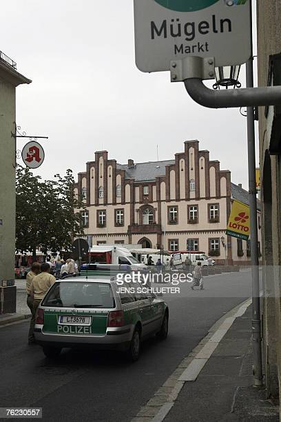 A police car stands on a road 23 August 2007 next to the market square in Muegeln eastern Germany where eight Indians were injured in an attack...