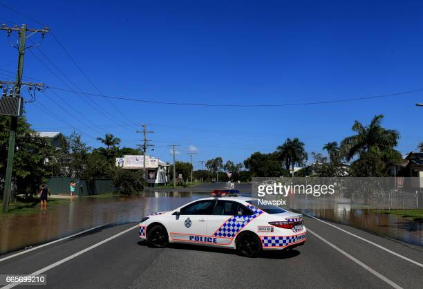 ROCKHAMPTON QLD A police car stops traffic driving through rising floodwaters at Depot Hill in Rockhampton Queensland after the Fitzroy River burst...