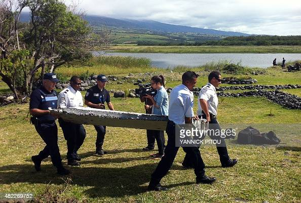 Police carry a piece of debris from an unidentified aircraft found in the coastal area of SaintAndre de la Reunion in the east of the French Indian...