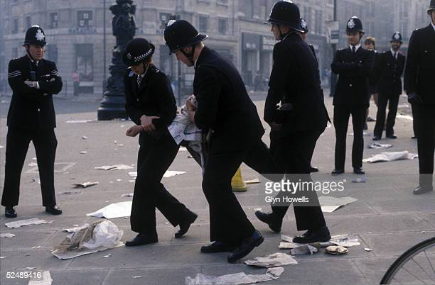 Police carry away a protestor at the Poll Tax riot in Trafalgar Square London 31st March 1990
