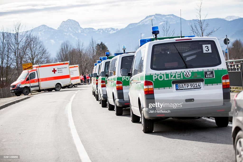Police cars and ambulances stand near the wreckage of two trains that collided head-on several hours before in Bavaria on February 9, 2016 near Bad Aibling, Germany. Authorities say at least nine people are dead and over 100 injured in the collision between two trains of the Meridian local commuter train service that occurred at approximately 7 am.