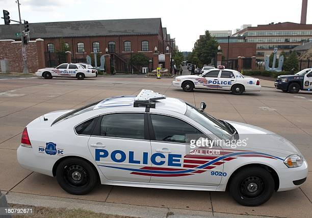 Police cars are parked outside Navy Yard following a shooting at the Navy Yard in Washington DC September 16 2013 A shooting rampage Monday at a US...