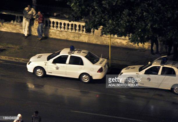 Police cars patrol Havana's waterfront to prevent any antigovernment action as fireworks are fired from Miami's boats on December 9 2011 Boats from...