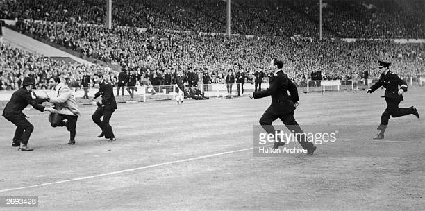 Police chase an Everton supporter across the pitch at Wembley after his team scored in the FA Cup Final Everton won beating Sheffield Wednesday 32...
