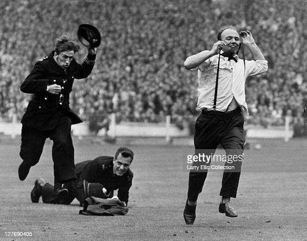 Police chase Everton supporter Eddie Kavanagh across the pitch at Wembley after his team scored in the FA Cup Final 14th May 1966 Everton won beating...