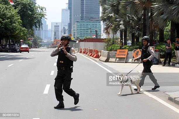 Police chase suspects thought to be hiding at a cafe after a series of blasts hit the Indonesia capital Jakarta on January 14 2016 A series of bombs...