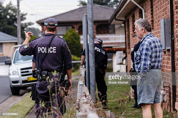 Police chat to residents in Salamader Pl Greenacre not far from the street where the burntout remains of a vehicle used during a shooting at...