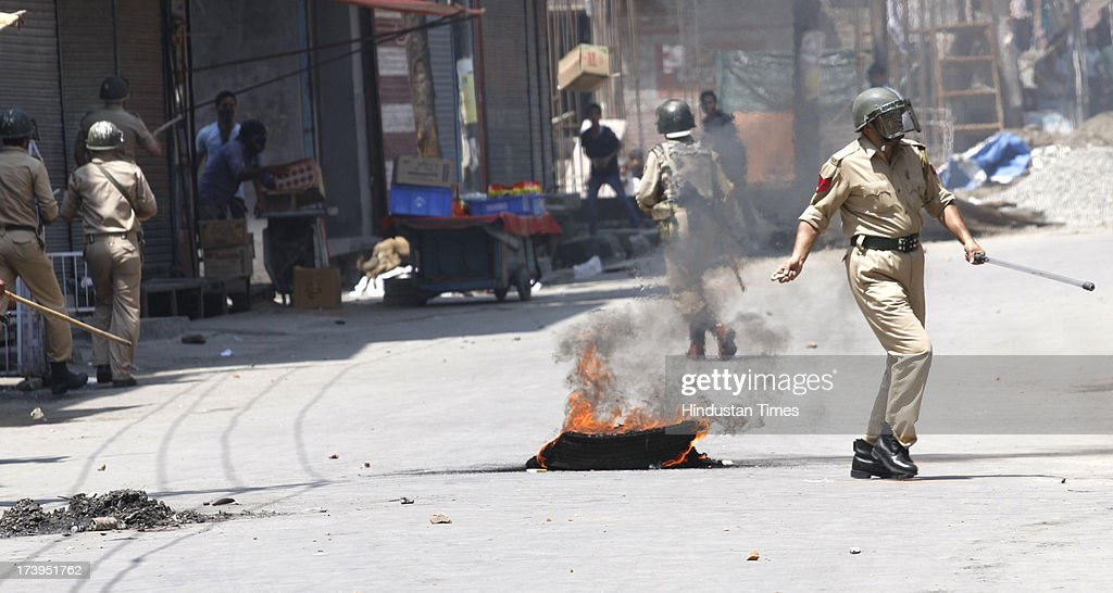 Police clash with protesters during a protest against killing of 4 people in BSF firing on July 18, 2013 in Srinagar, India. Four people were killed today when security personnel opened fire at a mob that had gathered at a BSF camp in Ramban district protesting against alleged manhandling of an Imam of the area by the force. Curfew would be imposed in Srinagar and all other major towns in the Kashmir Valley from Friday morning as a precautionary measure.