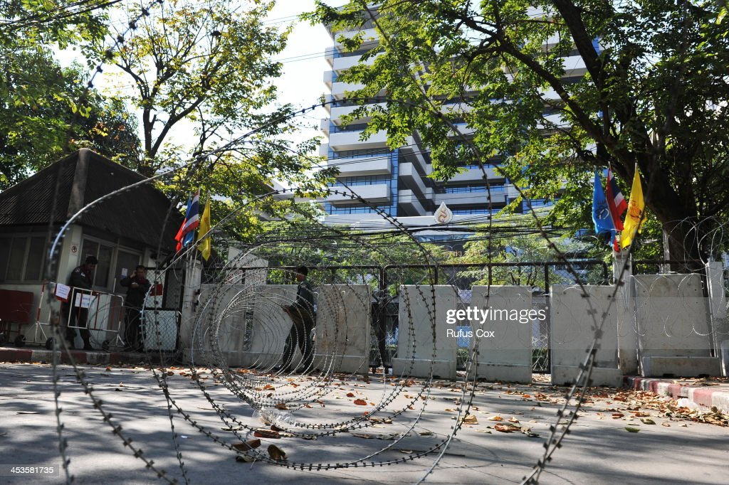 Police clear razor wire from a fortified entrance of the Royal Thai Police HQ amid easing tensions in the run up to the Thai king's birthday on December 4, 2013 in Bangkok, Thailand. In marking the king's birthday anti-government protesters have declared a temporary truce in their campaign to topple the government.