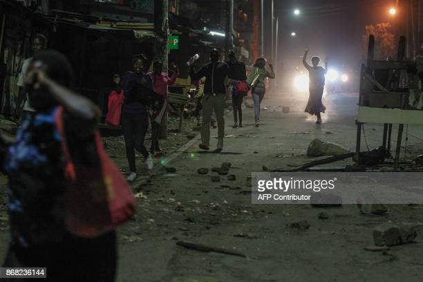 TOPSHOT Police clear the road as supporters of Kenya's opposition National Super Alliance block roads and burn tyres during a protest following the...