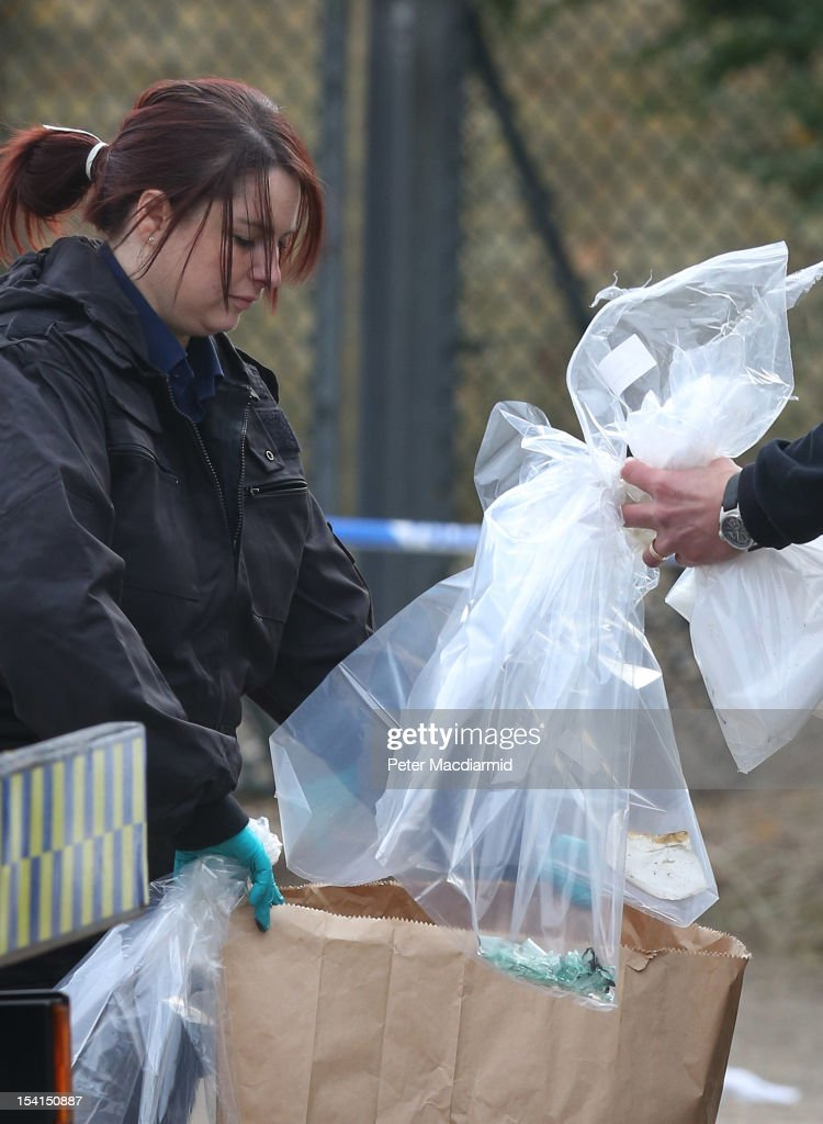 Police collect evidence at a house fire that killed five people on October 15, 2012 in Harlow, England. A woman and four children have died and another three are in hospital after a fire in a house on an estate near Harlow in Essex.