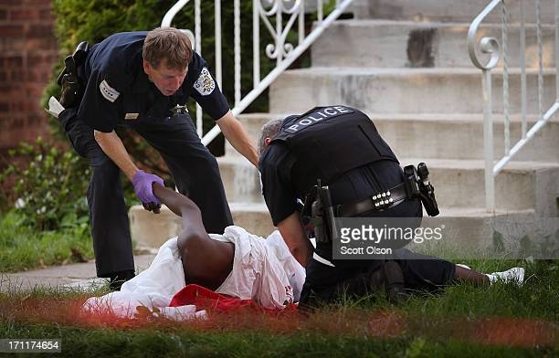 Police collect evidence at the scene of a shooting on June 22 2013 in Chicago Illinois One man was killed and two others were wounded in the shooting...