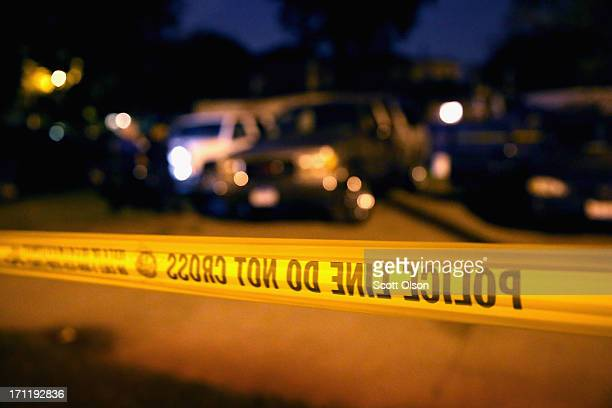 Police collect evidence at the scene of a shooting on June 23 2013 in Chicago Illinois A man was wounded in the leg when someone fired at least 11...