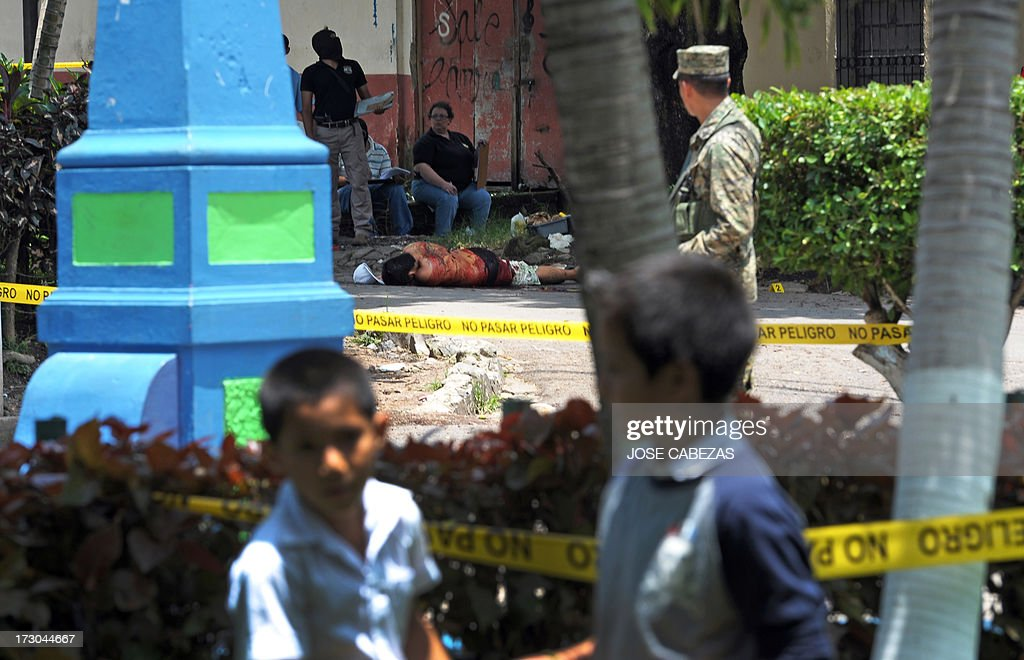 Police collect evidence beside a murdered man in the town of Quezalteque, 25 km west of San Salvador, on July 5, 2013. The victim, 19-year-old Carlos Ernesto Alvarez, a tuk-tuk driver, was killed allegedly by gang members when he was cleaning his vehicle. According to the forensic departament 66 people were murdered in El Salvador in a raise in violent deaths in the first four days of July. Murders had dropped after a gang truce was reached in March 2012. AFP PHOTO/Jose CABEZAS