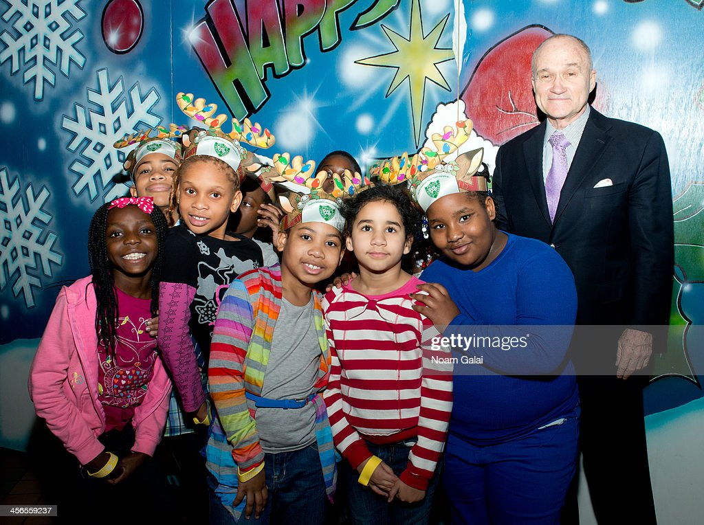 Police Commissioner Ray Kelly poses with kids at the 2013 CitySightseeing New York holiday toy drive at PAL's Harlem Center on December 14, 2013 in New York City.
