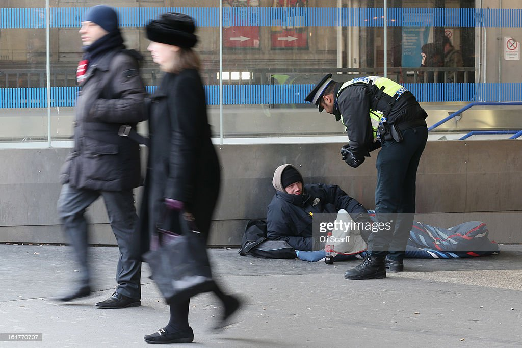 A police community support officer for the British Transport Police speaks to a man in a sleeping bag outside Victoria Station on March 27, 2013 in London, England.