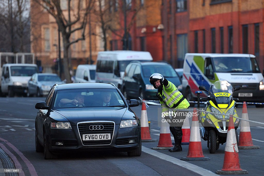 A police community support officer gives directions to a car carrying London Mayor Boris Johnson as he arrives near at scene of a helicopter crash in central London on January 16, 2013. Two people were killed when a helicopter hit a crane at a building site in central London during morning rush hour and plunged to the ground in a ball of flames. AFP PHOTO / CARL COURT