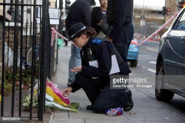 A police community support officer lays flowers handed to her at the scene in Eastway Hackney east London where a teenage girl named as Shereka Marsh...