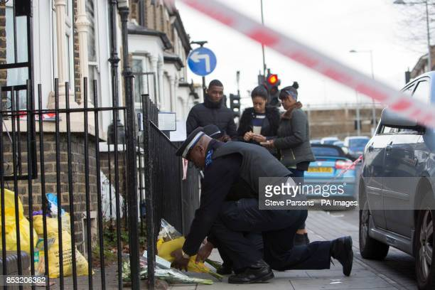 A police community support officer lays flowers handed to him at the scene in Eastway Hackney east London where a teenage girl named as Shereka Marsh...