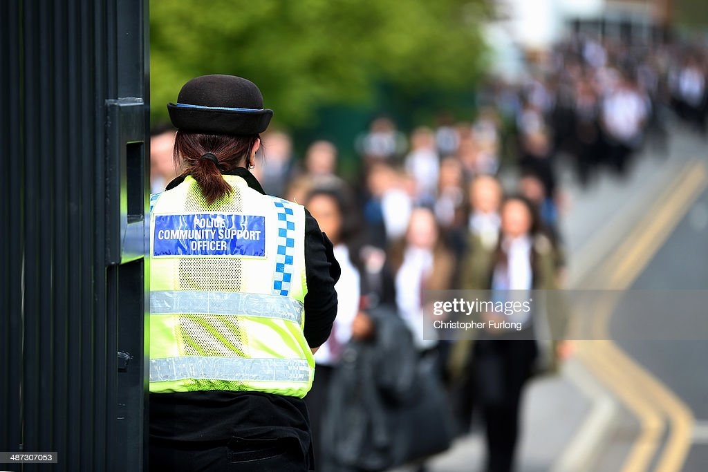 A police community support officer stands guard outside Corpus Christi Catholic College in Neville Road, as children leave at the end of the day on April 29, 2014 in Leeds, England. A fifteen year old male student has been arrested in connection with the death of teacher Anne Maguire, who was fatally stabbed yesterday during a lesson at Corpus Christi Catholic Catholic College.