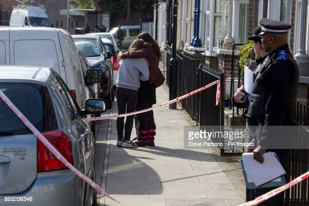 Police community support officers watch as two girls console each other at the scene in Eastway Hackney east London where a teenage girl named as...