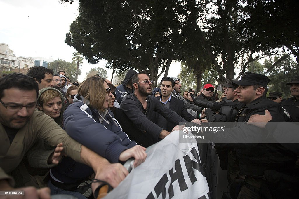 Police confront demonstrators attempting to pull down security barriers during a protest outside the Cypriot parliament in Nicosia, Cyprus, on Friday, March 22, 2013. The aid package Cyprus is seeking would only provide temporary relief as it risks triggering a capital flight that would push the nation closer to needing to restructure its debts. Photographer: Simon Dawson/Bloomberg via Getty Images