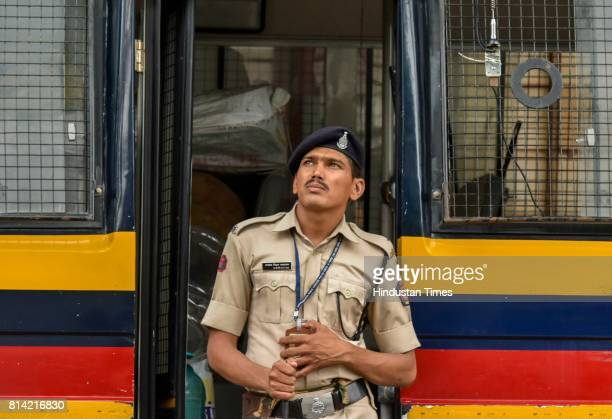 Police constable watching the digital broadcast on the facade of the Bombay Stock Exchange displaying the benchmark share index SENSEX crossing 32000...