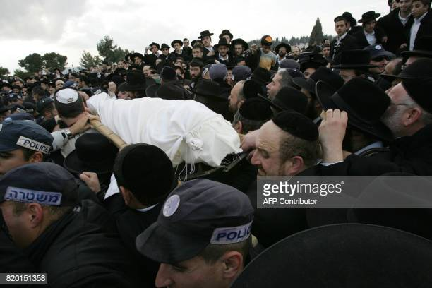 Police control the mourners as hundreds of faithful gather as the body of Rabbi Yitzhak Kaduri is taken for burial at the Givat Shaul cemetery in...