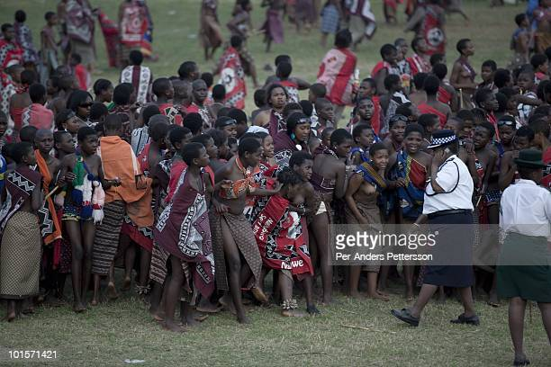 Police control young girls at a traditional Reed dance ceremony at the stadium at the Royal Palace on August 31 in Ludzidzini Swaziland About 80000...