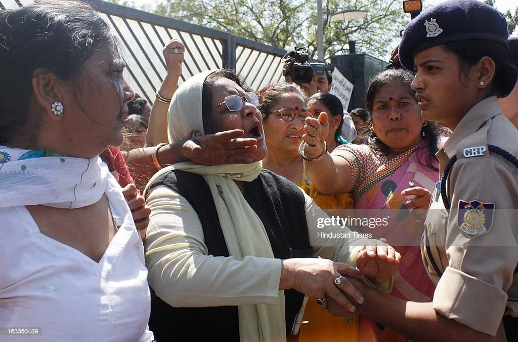 Police controlling BJP women activists who are protesting against the Delhi Chief Minister Sheila Dikshit for lack of safety for women in the city during a function oraganized at Talkatora stadium on the occasion of International Women's Day on March 8, 2013 in New Delhi, India. Sheila Dikshit was Chief guest of the event.