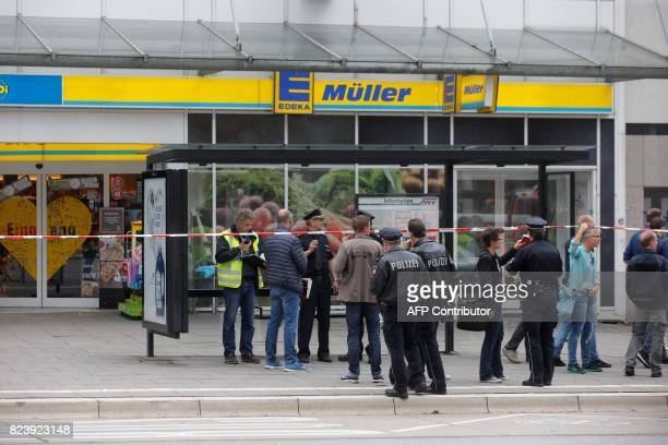 Police cordon off the area around a supermarket in the northern German city of Hamburg where a man killed one person and wounded several others in a...