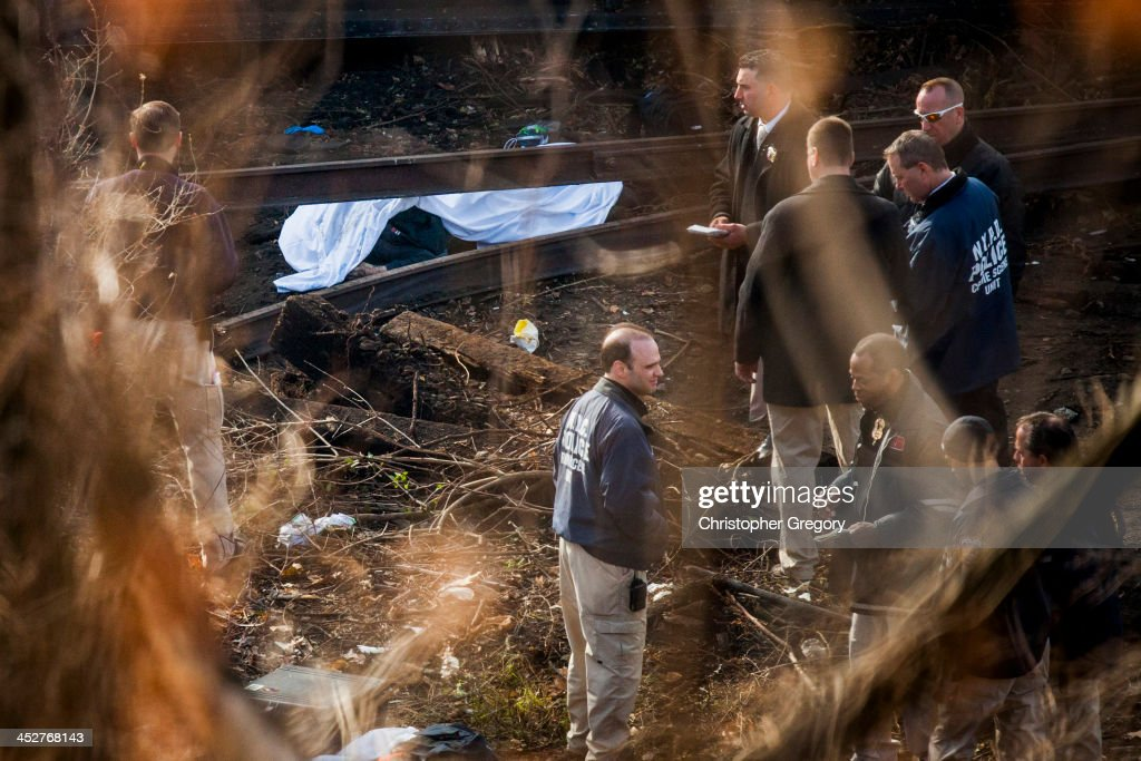 Police Crime Scene investigators stand near a covered body after a Metro-North commuter train derailed just north of the Spuyten Duyvil station December 1, 2013 in the Bronx borough of New York City. Multiple injuries and at least 4 deaths were reported after the seven car train left the tracks as it was heading to Grand Central Terminal along the Hudson River line.