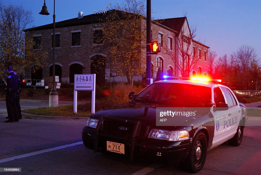 A police cruiser and two officers stand guard outside the Azana spa in Brookfield, Wisconsin, where a gunman killed three people and shot four others before killing himself on October 21, 2012. The suspect -- identified as 45-year-old Radcliffe Haughton -- was later found dead at the scene, police told AFP. He was believed to have shot himself.He was believed to be in the midst of an ugly divorce with his wife, who worked at the suburban Milwaukee day spa. AFP PHOTO/Mira OBERMAN