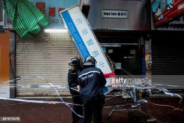 Police deal with a damaged light board as typhoon Hato hits Hong Kong on August 23 2017 in Hong Kong Hong Kong Hong Kong's weather authorities raised...