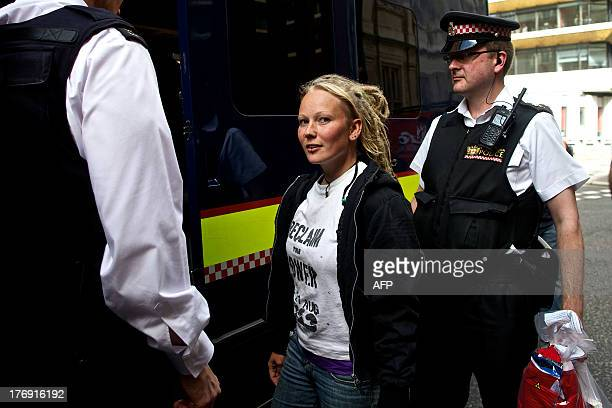 Police detain a climate protester after she and other demonstrators blocked the entrance to the office building housing PR company Bell Pottinger who...